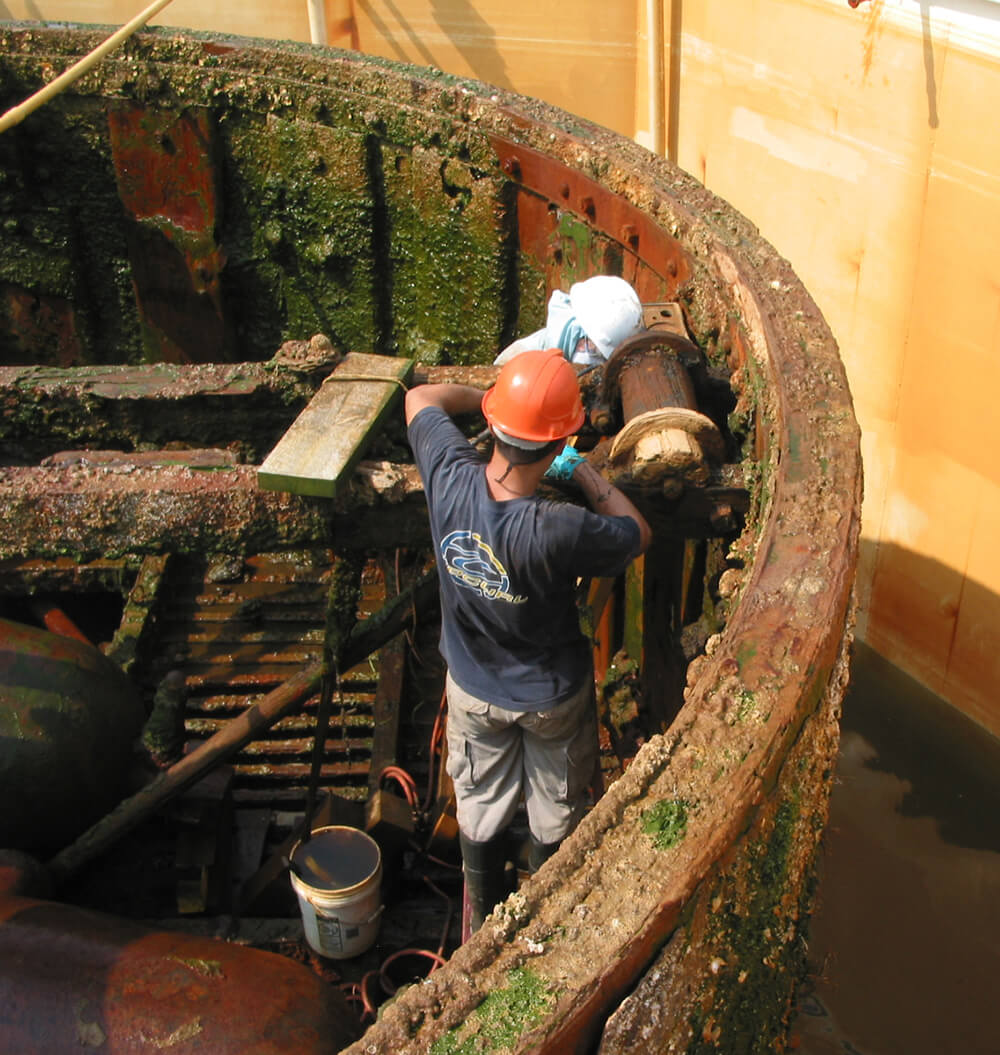 conservators work on the turret ring of the monitor