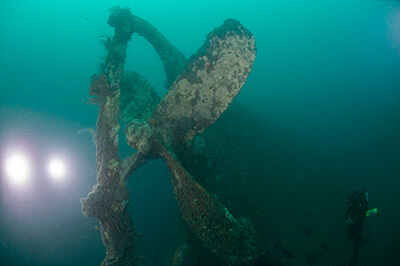A diver inspects Merak's propeller and rudder post